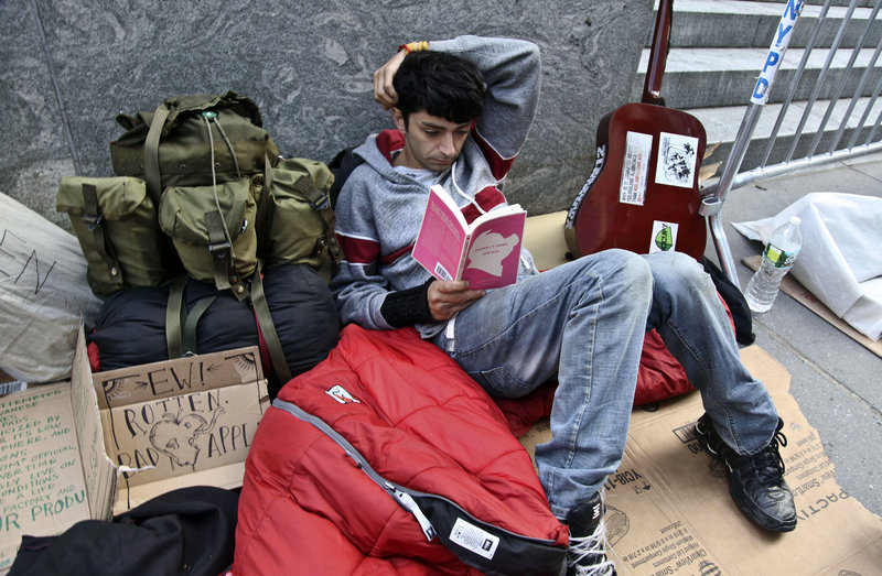 Joseph Cruz, 19, waits in line Thursday outside Apple's Fifth Avenue store in New York City. Cruz, who started camping out last Friday, is not seeking easy cash or publicity – he just wants to get his hands on the new iPhone 5.