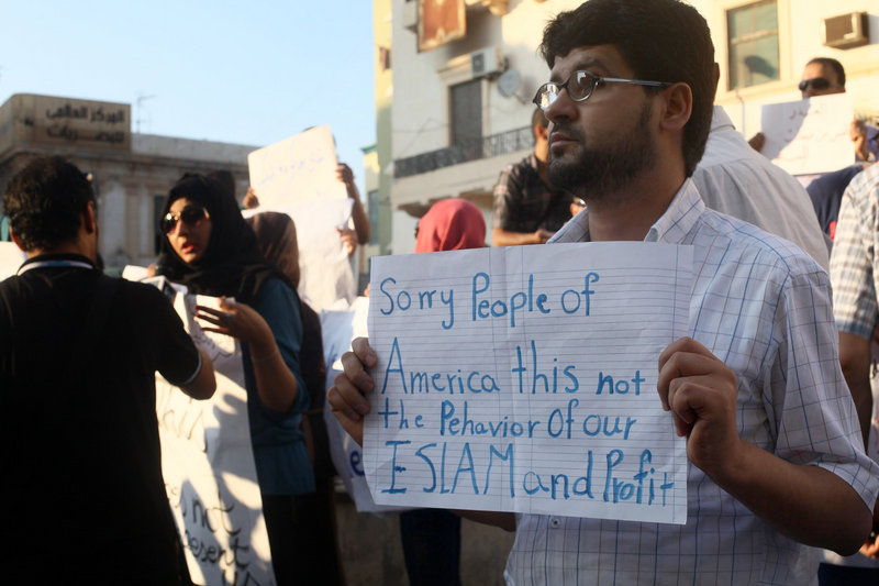 A Libyan man holds a placard in English while demonstrating Sept. 12 against the attack on the U.S. consulate that killed four Americans in Benghazi, Libya.
