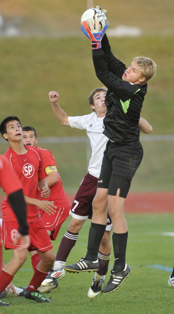 South Portland goalkeeper Ben Burkey takes command in the penalty area, hauling in a shot in front of Marc Reynolds of Windham.