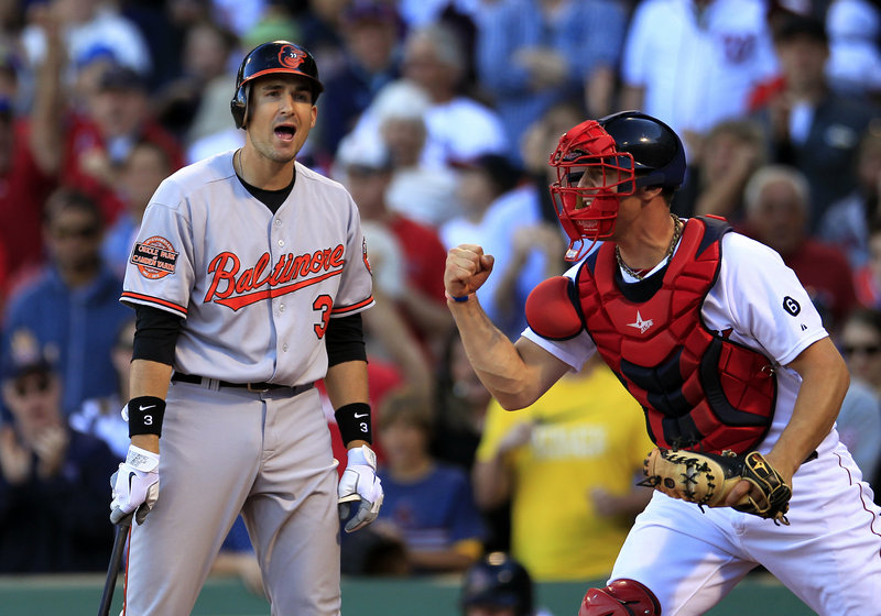 Baltimore Orioles batter Ryan Flaherty reacts after striking out to end Sunday's game as Red Sox catcher Ryan Lavarnway celebrates the 2-1 Boston victory at Fenway Park.