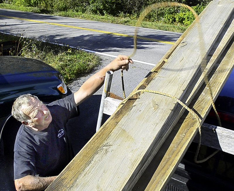 Adrian Hooydonk unties lumber from his pickup truck last week at his home in Spruce Head. The lobster buyer doesn't approve of everything President Obama has done, but blames Republicans for being obstructionist.