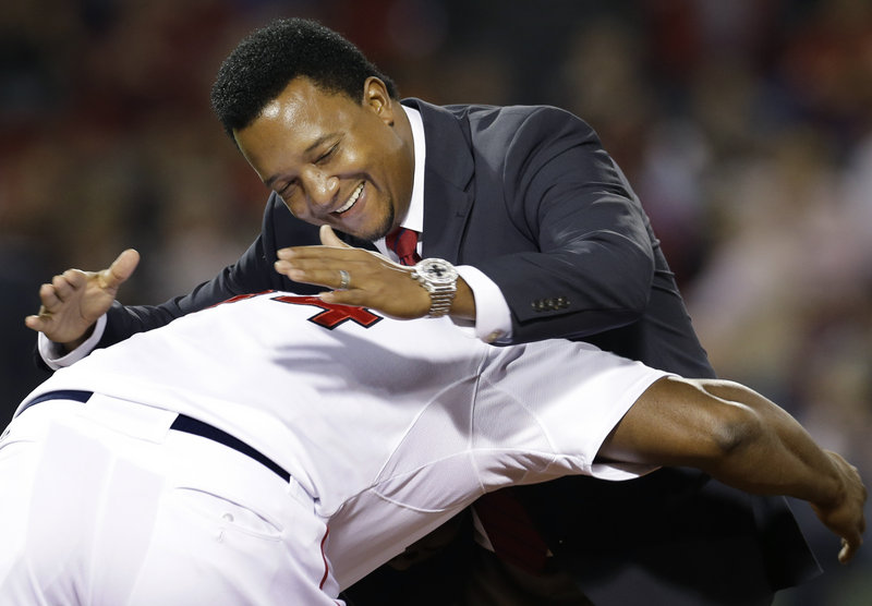 Pedro Martinez is greeted by David Ortiz – teammates when the Red Sox were contenders – during a ceremony Wednesday night honoring the top 40 players in franchise history.