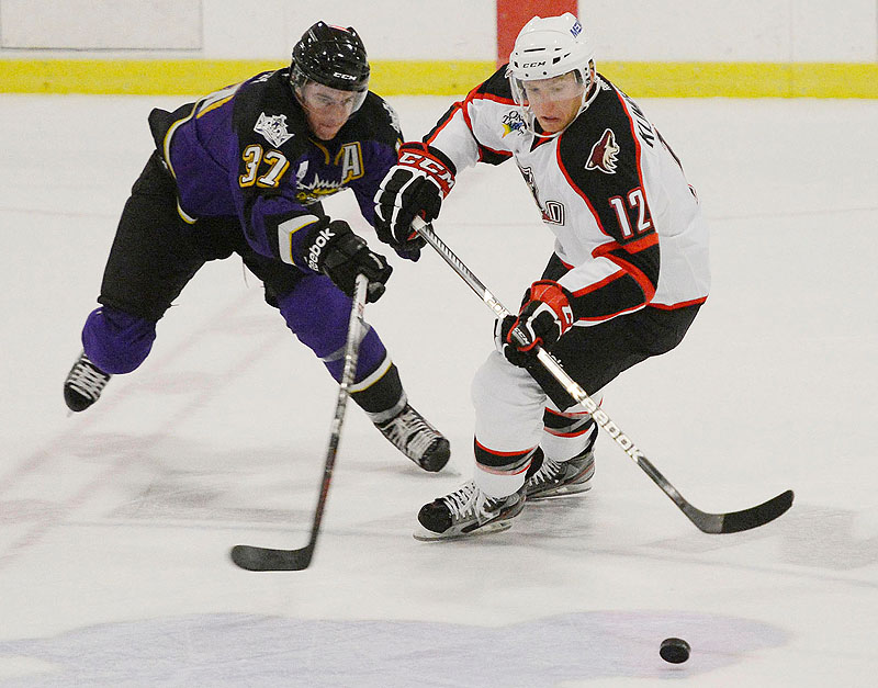 Thomas Hickey of Manchester battles for the puck with Portland's Rob Klinkhammer in an exhibition game Sunday at the Portland Ice Arena. The Pirates lost to the Monarchs on Monday for the second time in as many days.