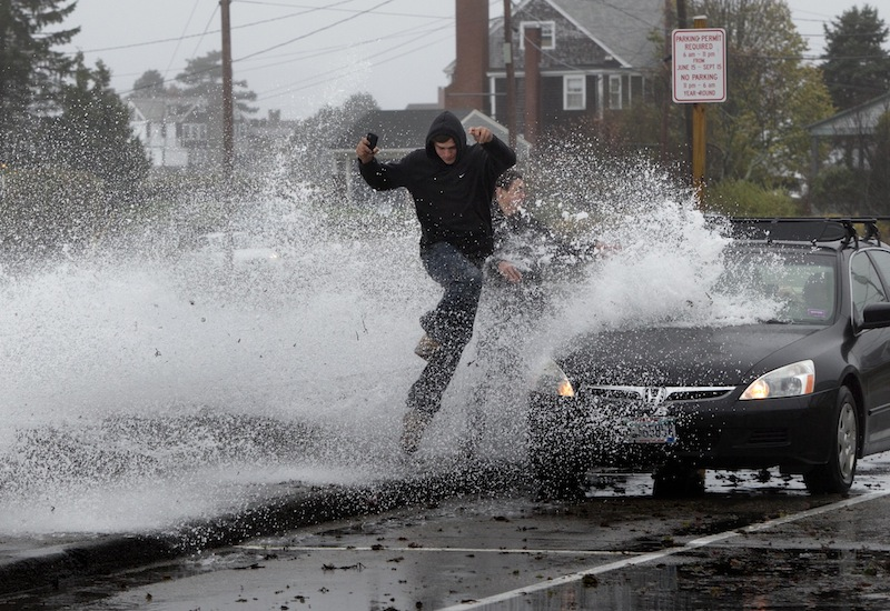 Caleb Lavoie, 17, of Dayton, Maine, front, and Curtis Huard, 16, of Arundel, Maine, leap out of the way as a large wave crashes over a seawall on the Atlantic Ocean during the early stages of Hurricane Sandy on Monday.