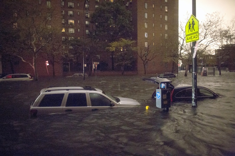 Vehicles are submerged on 14th Street near the Consolidated Edison power plant, Monday, Oct. 29, 2012, in New York. Sandy continued on its path Monday, as the storm forced the shutdown of mass transit, schools and financial markets, sending coastal residents fleeing, and threatening a dangerous mix of high winds and soaking rain.  (AP Photo/ John Minchillo)
