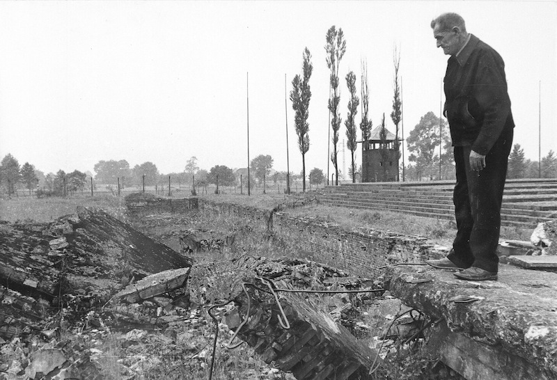 In this undated file photo from 1979, a former inmate of the Nazi concentration camp at Auschwitz-Birkenau, Poland, looks at ruins of gas chambers where hundreds of people were killed during World War II. The oldest known survivor of Auschwitz, a teacher who gave lessons in defiance of Nazi occupiers, has died at the age of 108. Antoni Dobrowolski died Sunday in the Polish town of Debno.