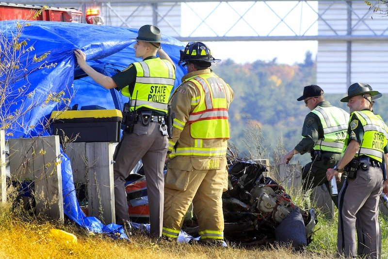 Police and fire officials examine a small plane that crashed, Thursday, Oct. 25, 2012 in Hookset, N.H. New Hampshire state police say a man and a woman died in the crash near Interstate 93 in Hooksett, N.H. (AP Photo/Jim Cole)