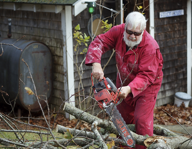 Bill Gribbin, 72, of Littlejohn Island, Yarmouth, cuts up a large tree limb that had fallen into his yard during the storm.