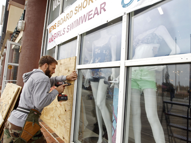 A worker boards up the windows of the store as Hurricane Sandy approaches in Ocean City, Md., on Saturday.
