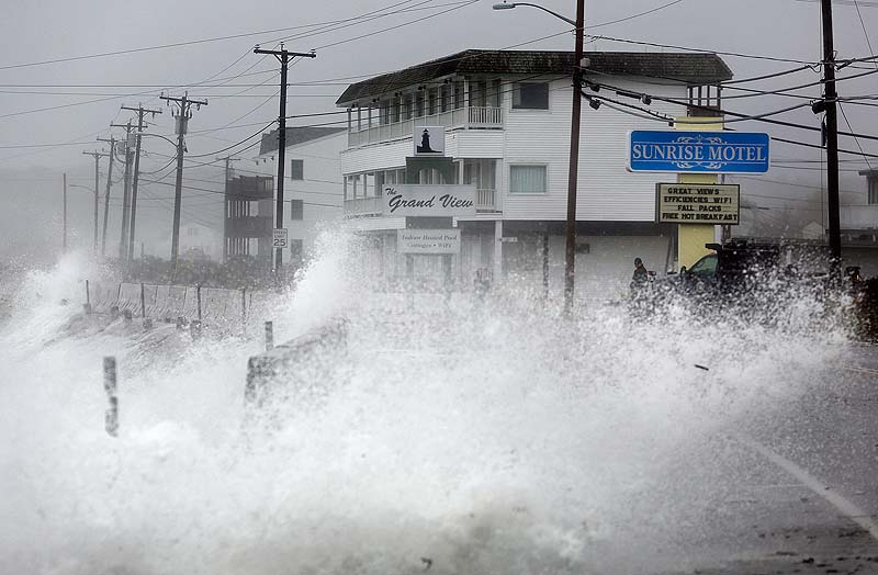Waves crash over a sea wall along Long Beach Avenue in York, Monday, Oct. 29, 2012, as a result of weather conditions from Hurricane Sandy.