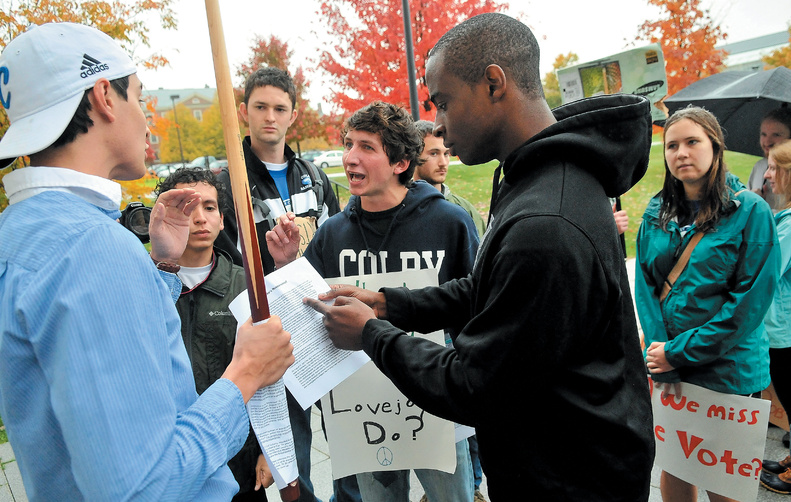 Anti-Diamond protesters Shelby O'Neill, center, a Colby College sophomore, and Uzoma Orchingwa, a Colby senior, right, talk with Colby junior and counterprotester Steve Carroll, left, outside the Diamond Building during Saturday's protest on the college green.