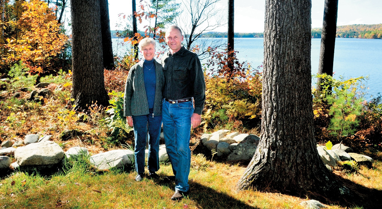 Phyllis and Lynn Matson stand beside a wooded buffer zone between their home and Long Pond in Rome. The buffer helps restict erosion that contains phosphorus and other nutrients that can adversely affect the water. The Matsons received a LakeSmart award for their efforts.