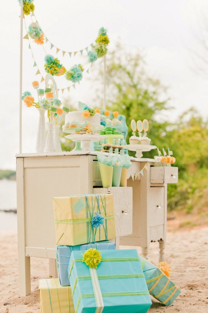 "Designers and stylists Maureen Anders and Adria Ruff used a palette of mint, aqua, yellow and lime green for a gender-neutral baby shower. They incorporated handmade elements like wool pompoms and used paper, marshmallows and cake decorations to create centerpiece ""flowers."""