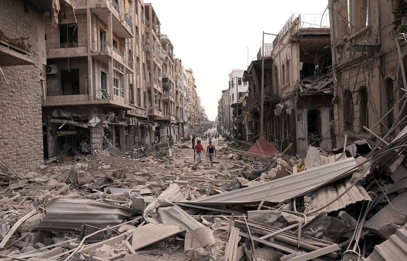Survivors walk amid the ruins of Saadallah al-Jabrisquare in Aleppo, Syria, on Wednesday. The government blamed its opponents for the huge blasts.