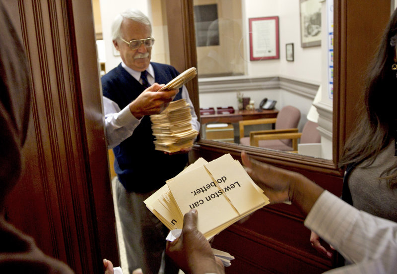 Petitions asking for his resignation of the mayor of Lewiston, Maine, are delivered City Administrator Ed Barrett, Thursday, Oct. 4, 2012, in Lewiston, Maine. Many community members are upset about comments the mayor made about Somali refugees in his city. (AP Photo/Robert F. Bukaty)