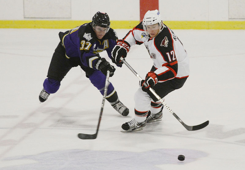 Rob Klinkhammer, right, of the Pirates tries to get around Manchester's Thomas Hickey during Sunday's preseason game at Portland Ice Arena.