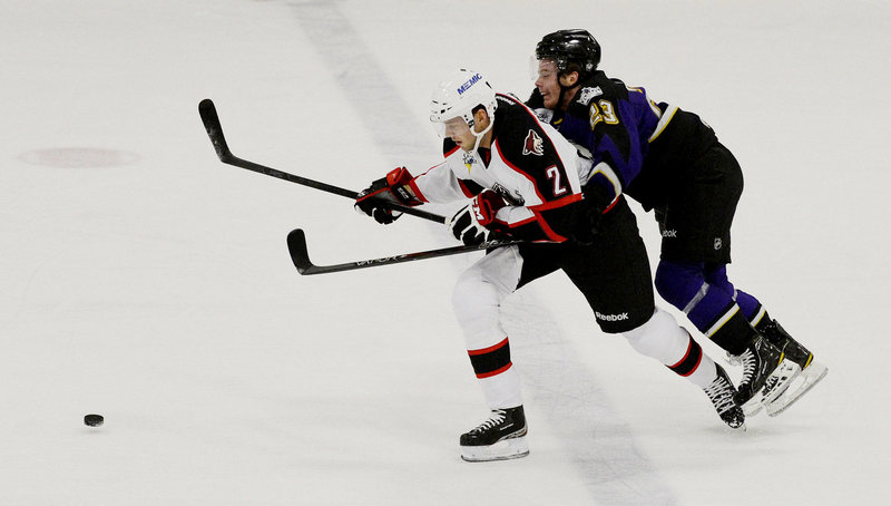Pirates defenseman David Rundblad chases the puck ahead of Manchester's Brian O'Neill, who scored the overtime goal that gave the Monarchs a 4-3 preseason win Sunday at Portland Ice Arena.