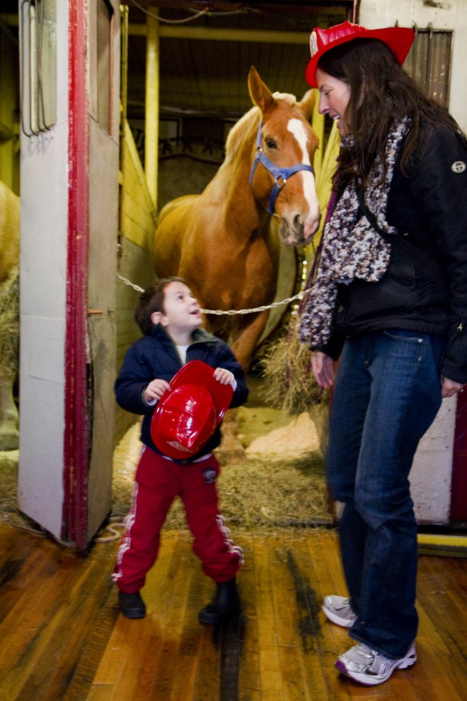 "Oscar Goss, 4, of Portland talks with his mother, Stephanie, during an open house at the Portland Fire Museum on Saturday. Oscar and his family come to the Spring Street museum often, but he likes the open house because of the ""neigh-neighs,"" his name for the horses."