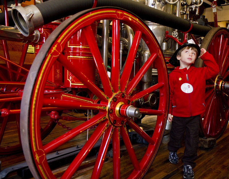 Senya Rogers-Kaufman, 5, of Portland checks out some antique firefighting equipment.