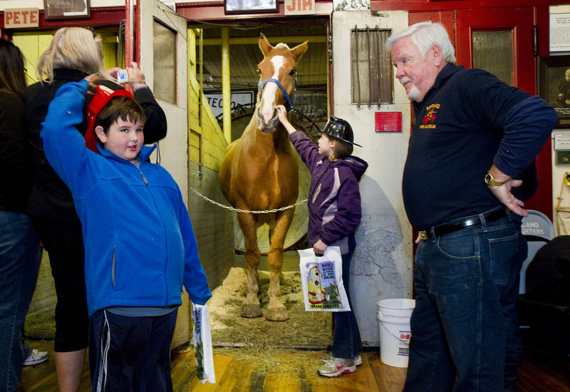 "Simon Girard, 7, of Old Orchard Beach poses questions to retired Portland firefighter John ""Smokey"" Chandler during an open house at the Portland Fire Museum on Saturday. Alison Blow, 10, of Biddeford, pets Jim the horse."