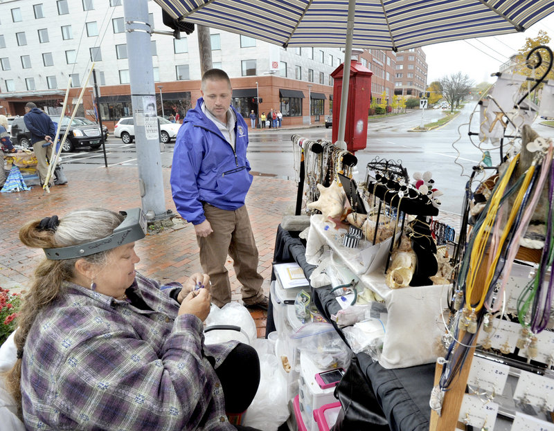 Chuck Fagone, Portland's code enforcement officer, patrols vendors, including Crystal Tripp of Bridgton, along Commercial Street on Saturday. Vendors can take up no more than 12 square feet of space while leaving at least 4 feet of sidewalk for pedestrians.