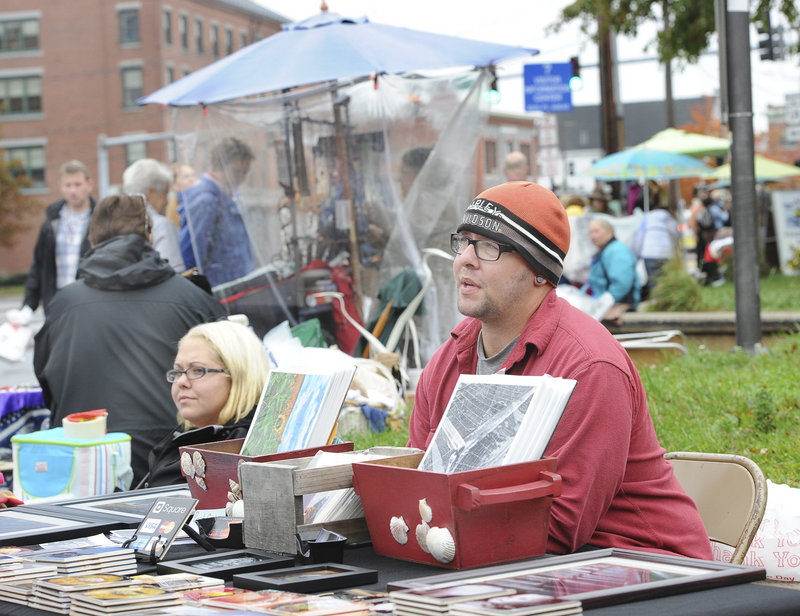 Amy Hague of Buxton and Al Farrisio of Fort Myers, Fla., sells their wares on Commercial Street in Portland on Saturday. More than 60 merchants have signed a petition asking the city to crack down on street vendors.