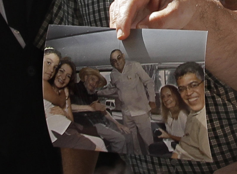 """Former Venezuelan Vice President Elias Jaua shows a picture of Cuba's retired president, Fidel Castro, third from left, at the Hotel Nacional in Havana on Sunday. According to Jaua, the picture was taken Saturday inside a van outside the hotel and shows Castro looking """"very well."""""""