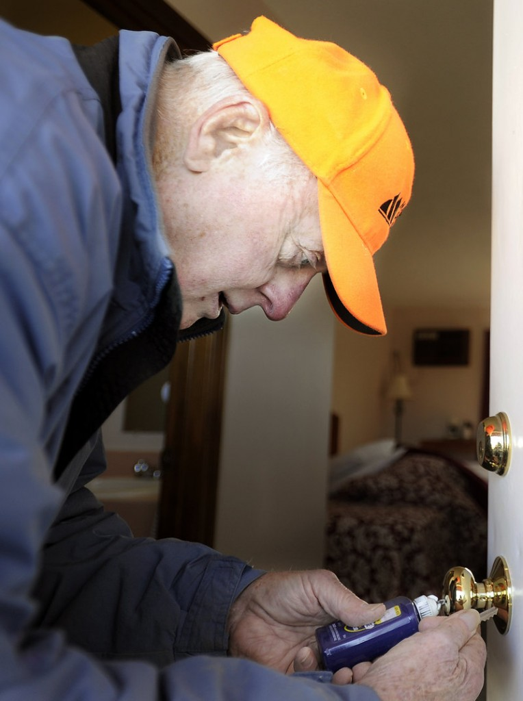George Gendron, a maintenance manager at the Machias Motor Inn, repairs a door handle to a hotel room Wednesday. Gendron says he'll vote for Mitt Romney in the presidential election.
