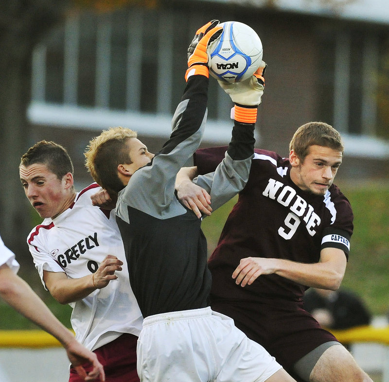 Greely goalkeeper Elijah Leverett pulls down a shot Wednesday night over his teammate, Joe Saffian, left, and Josh Davis of Noble during Greely's come-from-behind 5-1 victory in a Western Class A boys' soccer quarterfinal at Cumberland.