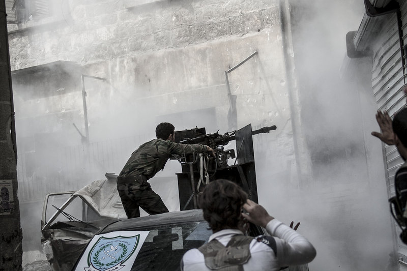 A Free Syrian Army fighter fires as rebels belonging to the Liwa Al Tawhid group carry out a military operation at the Karmal Jabl front line in Aleppo, Syria.