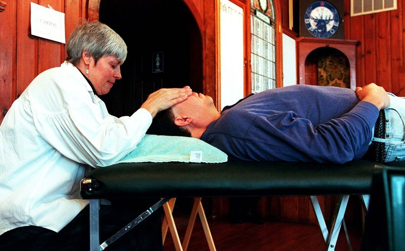 """A therapist provides a Reiki treatment at a 1997 Psychic/Holistic Fair in Saco. A Reiki master says many hospitals now offer the """"gentle and non-invasive"""" therapy."""