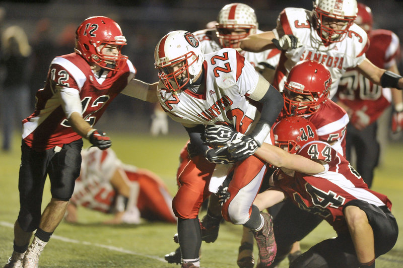 Sanford running back Alex Shain, 22, drags Scarborough defenders for a short gain Friday night. Shain ran for 148 yards, all but 42 in the first half.