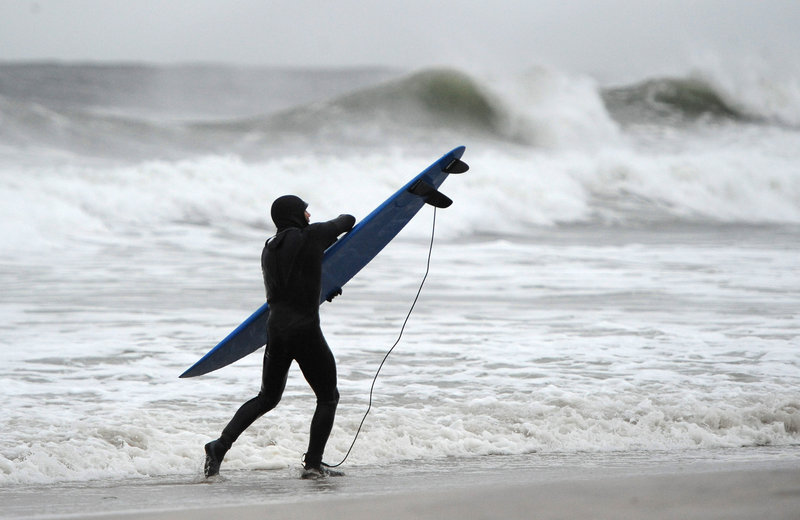 A surfer holds tight to his board against the strong winds and high surf of the Atlantic Ocean before the arrival of Hurricane Sandy on Sunday in Long Beach, N.Y.