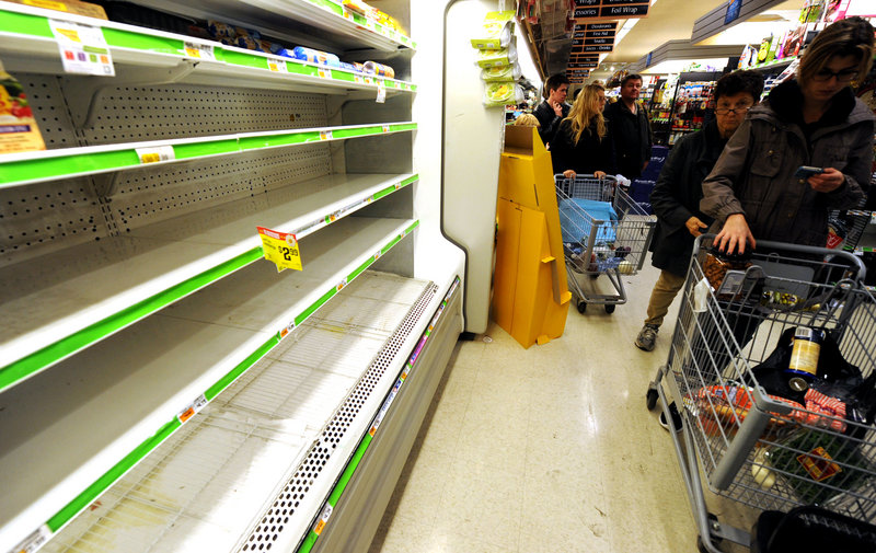 Customers shop for food in Manhattan on Sunday. Hundreds of thousands were ordered to evacuate coastal areas, including 375,000 in lower Manhattan and other parts of New York.