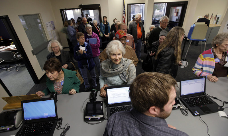 Voters wait for their ballots on Sept. 27, the first day of early voting for the November presidential election in Des Moines, Iowa. About 35 percent of voters nationwide are expected to cast their ballots before Election Day, Nov. 6, either in person or by mail.