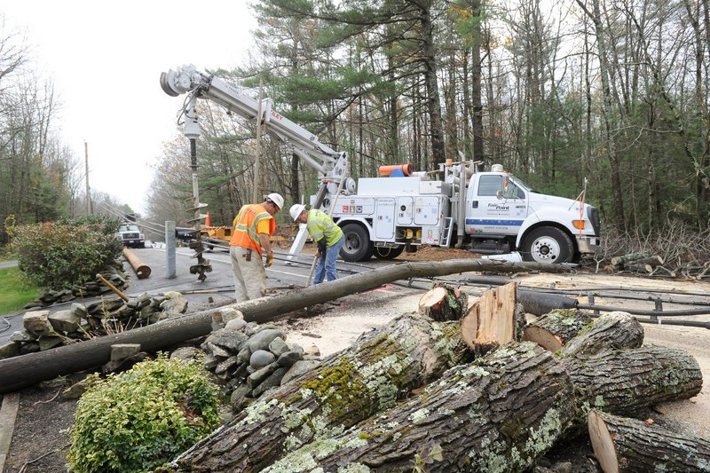 Fairpoint employees Mike Pallozzi and Dennis Buhelt, above and below, replace a utility pole on Methodist Road in Westbrook on Tuesday after Hurricane Sandy rolled through Maine.