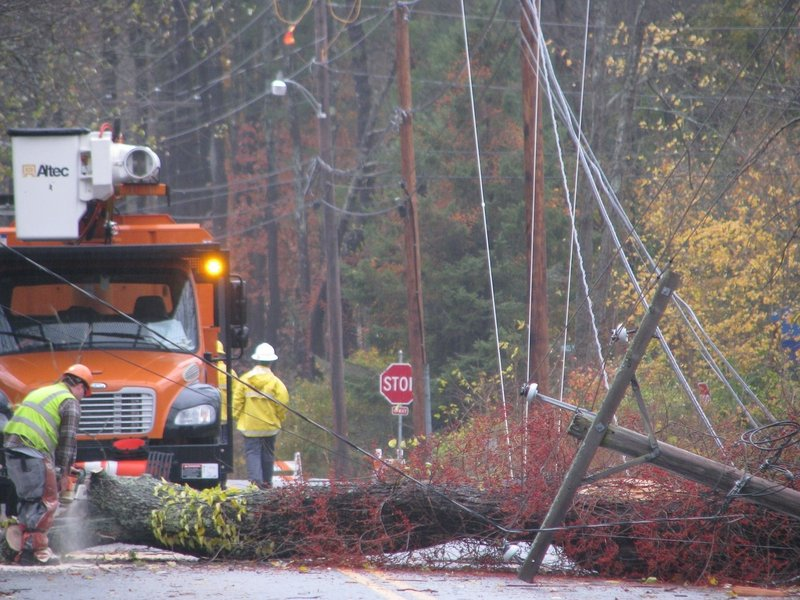 Crews from McDonough Electric Construction of Bedford, Mass., work to remove a cherry tree that had fallen over Princes Point Road in Yarmouth on Tuesday.