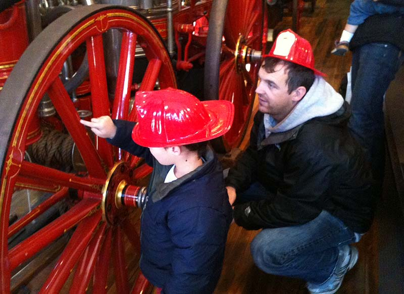 Oscar Goss, 4, and his father, Amos, of Portland check out one of the antique fire engines during an open house at the Portland Fire Museum on Saturday.