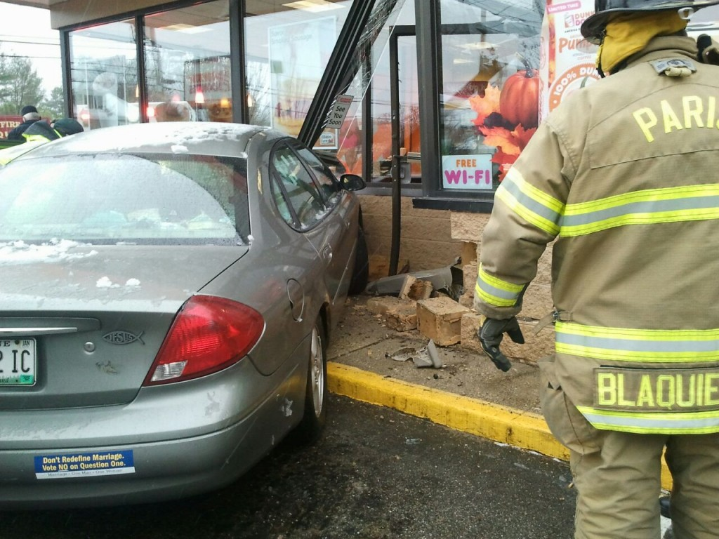 A responder looks over the damage where a car ran into the entrance of the Dunkin' Donuts in Paris, Maine, on Thursday.