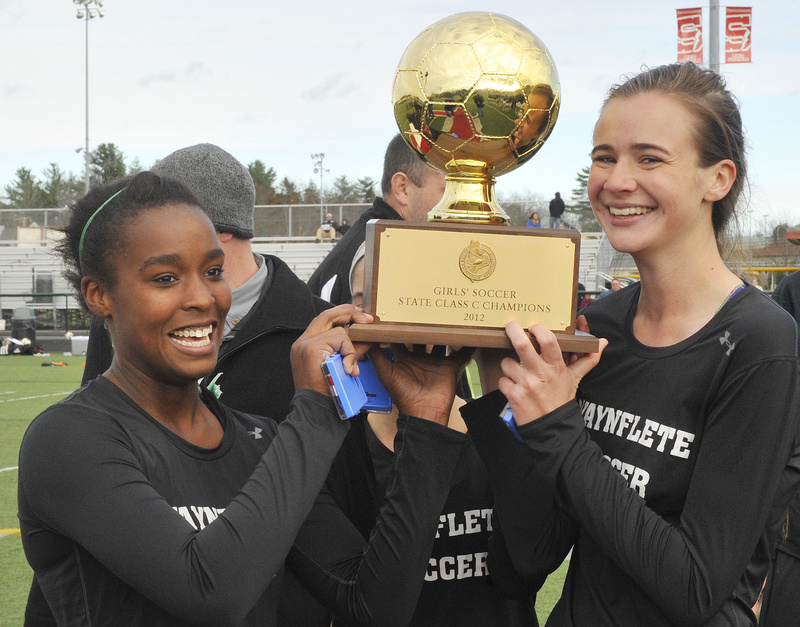 Waynflete captains Rhiannan Jackson, left, Katherine Harwood and Sadie Cole hold the girls' Class C soccer championship trophy following a 3-2 win over Fort Kent Saturday at Scarborough.