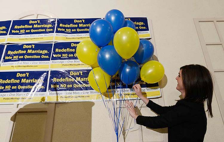 Megan Hutson with Protect Marriage Maine sets up the stage at the Ramada Conference Center in Lewiston on Tuesday.