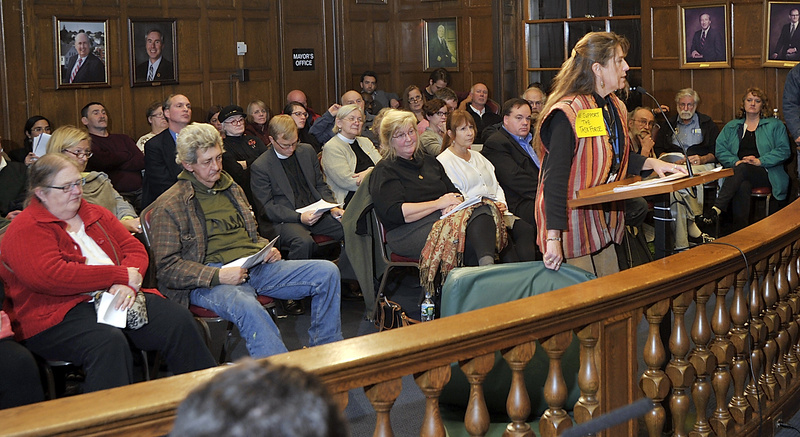 Donna Yellen, advocacy director at Preble Street in Portland, holds the type of mattress on which homeless people sleep, while she address a City Council meeting Monday. The meeting was not the fight some people were expecting between the business community and advocates for the homeless.