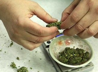 FILE - In this Oct. 10, 2012 file photo, marijuana is weighed and packaged for sale at the Northwest Patient Resource Center medical marijuana dispensary in Seattle. Pot, at least certain amounts of it, will soon be legal under state law in Washington and Colorado. Now, officials in both states are trying to figure out how to keep doped drivers off the road. (AP Photo/Ted S. Warren, File)