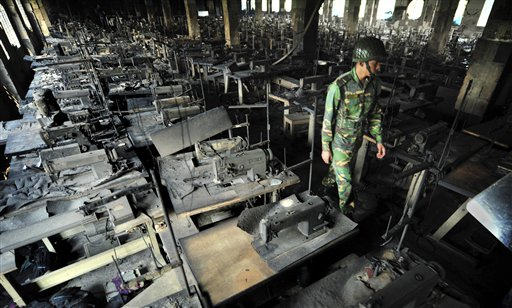 A Bangladeshi police officer walks between rows of burnt sewing machines in a garment factory outside Dhaka, Bangladesh on Sunday. At least 112 people were killed in a late Saturday night fire that raced through the multi-story garment factory just outside of Bangladesh's capital.