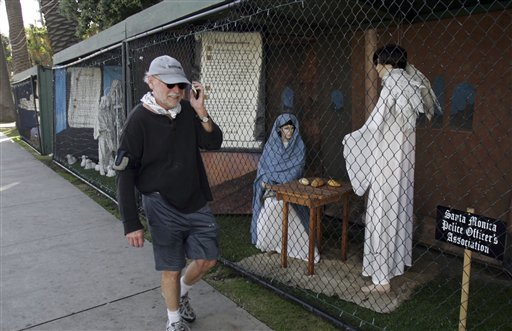 A man walks past two of the traditional nativity scenes at Palisades Park in Santa Monica, Calif., in December 2011. The city eliminated the holiday tradition this year rather than see a repeat of disputes and vandalism related to competing messages of Christians and atheists.