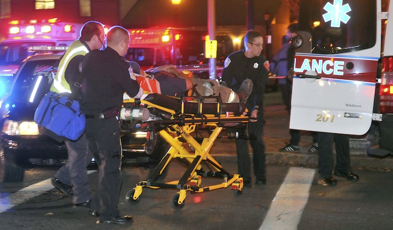 An injured firefighter is wheeled from the scene after a building was leveled by an explosion in downtown Springfield, Mass. on Friday, Nov. 23, 2012. (AP Photo/Springfield Republican, Don Treeger)
