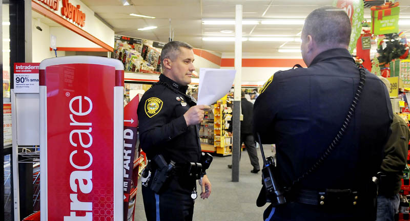 Augusta police confer Wednesday inside the CVS pharmacy on Capitol Street in Augusta, after a narcotics robbery.