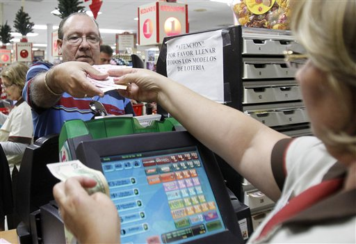 Maria Diaz, right, sells a customer Powerball tickets at a local supermarket in Hialeah, Fla., on Tuesday. There has been no Powerball winner since Oct. 6, and the jackpot already has climbed to more than $500 million, the second-highest jackpot in lottery history, behind only the $656 million Mega Millions prize in March.