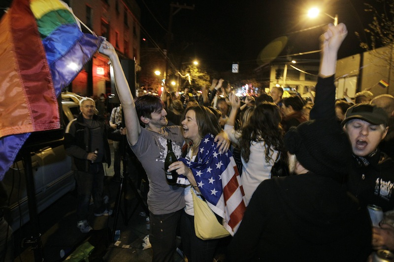 Revelers display U.S. and gay pride flags as they celebrate early election returns favoring Washington state Referendum 74, which would legalize gay marriage, during a large impromptu street gathering in Seattle's Capitol Hill neighborhood, in the early hours of Wednesday, Nov. 7, 2012. The re-election of President Barack Obama and Referendum 74 drew the most supporters to the streets. (AP Photo/Ted S. Warren)