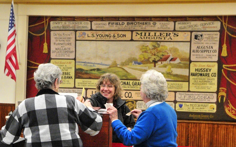 Melissa Morrill, center, chats with election workers Joan Moore, left, and Carolyn Greenwood as she casts her ballot around 5:45 p.m. Tuesday at the Windsor town office.